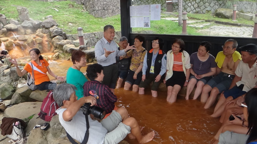 服務人員於泡腳池與遊客互動(張文清攝)